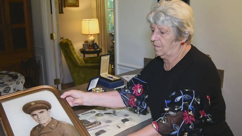 Lucy Howe holding a photograph of her uncle Sgt. Elwood Truslow