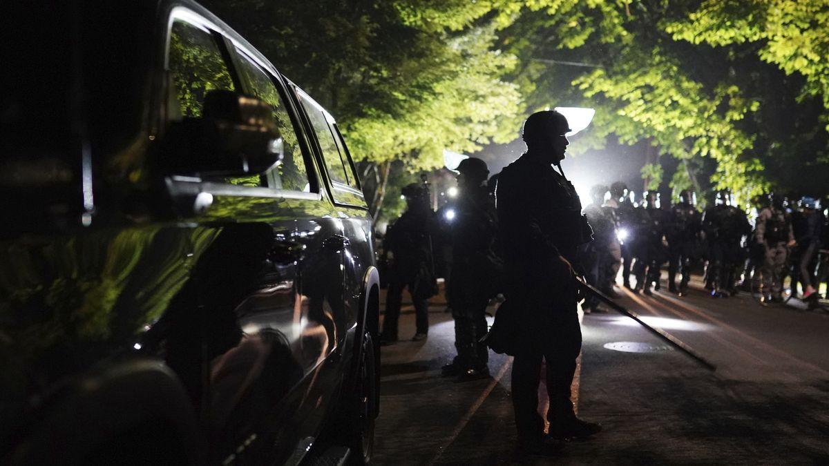Portland police officers walk through the Laurelhurst neighborhood after dispersing protesters...