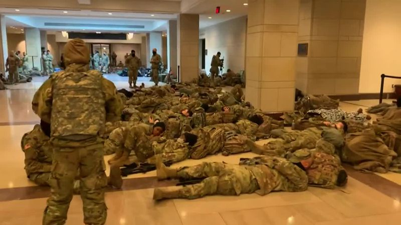 Images shared online and on the news show members of the National Guard resting on the floor of...