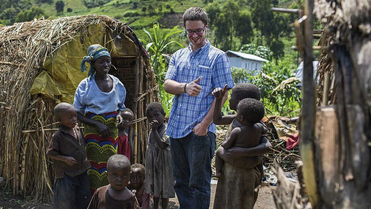 Michael Sharp visits with Elizabeth Namavu and children in Mubimbi Camp, home to displaced persons in the Democratic Republic of Congo. A coordinator for the Mennonite Central, he has an unusual approach to peacemaking.<br />Credit: Jana Asenbrennerova/Courtesy of MCC