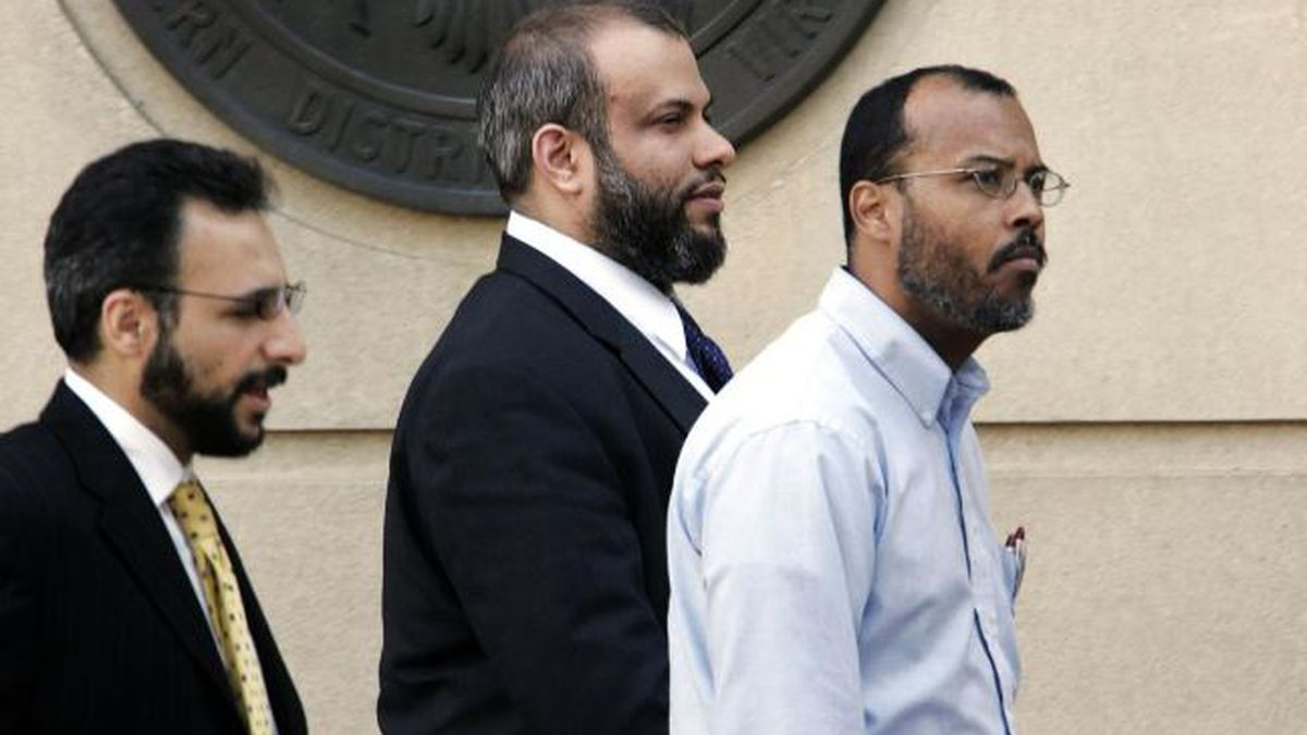 FILE - In this April 18, 2005 file photo, Ali Al-Tamimi, center, walks with two unidentified men, as he leaves the Albert V. Bryan Courthouse, in Alexandria, Va. A federal judge may toss out parts of a 10-count conviction against the Islamic scholar serving life in prison for persuading some followers to try to join the Taliban after the Sept. 11 attacks. The review in the case of Al-Timimi, of Virginia, comes after a Monday, June 24, 2019 ruling by the Supreme Court striking down part of a federal law regulating crimes of violence as unconstitutionally vague. Judge Leonie Brinkema on Tuesday, June 25 asked prosecutors to explain why she shouldn't overturn three of the counts. (AP Photo/Manuel Balce Ceneta, File)