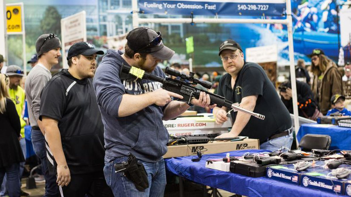 A vendor looks on as a customer handles a scoped rifle at a gun show on Sunday, March 25. A majority of vendors, including the one pictured, owned retail stores around Virginia and traveled to the Richmond show with a smaller selection to sell. (Photo by Erin Edgerton)