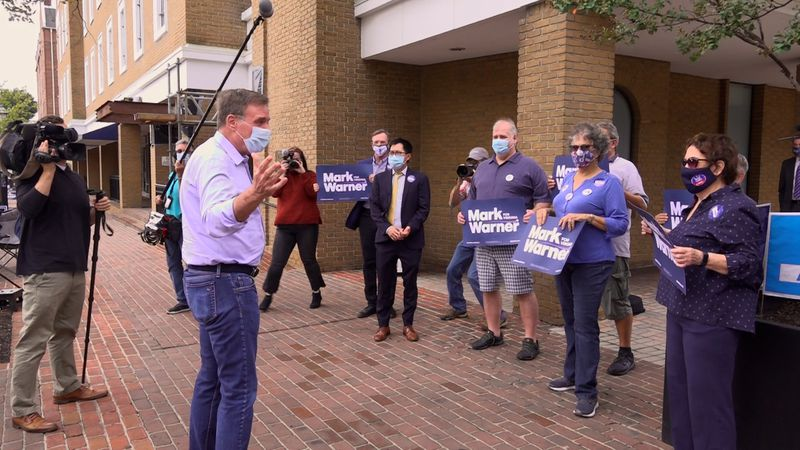 Sen. Mark Warner greets supporters in Alexandria as polls open for early voting in Va.