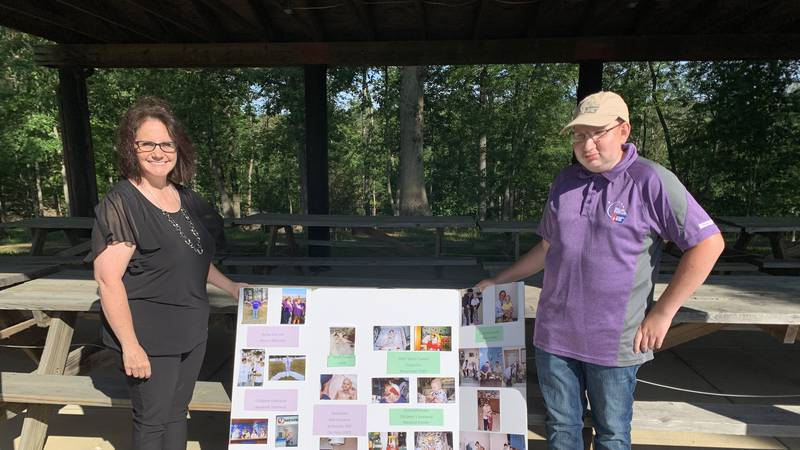 Alex and his mother Vicki in front of their memory board showing his battle with cancer.