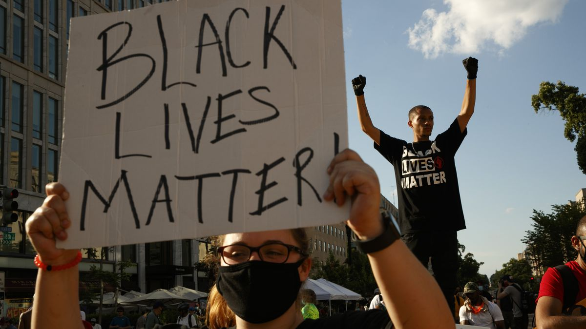 In this June 24, 2020, file photo, Antonio Mingo, right, holds his fists in the air as demonstrators protest in front of a police line on a section of 16th Street that's been renamed Black Lives Matter Plaza, in Washington. Thousands of Black activists from across the U.S. will hold the 2020 Black National Convention on Aug. 28, 2020, via livestream to produce a new political agenda that builds on the protests that followed George Floyd's death. Organizers of the gathering shared their plans with The Associated Press on Wednesday, July 1, ahead of an official announcement.