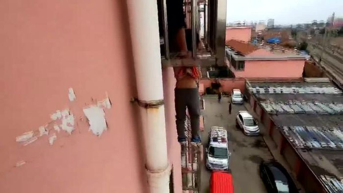 Firefighters in China rescued a 4-year-old boy whose head became stuck in a window's guard rail, leaving him hanging four stories above ground.(Source: CCTV/CNN)