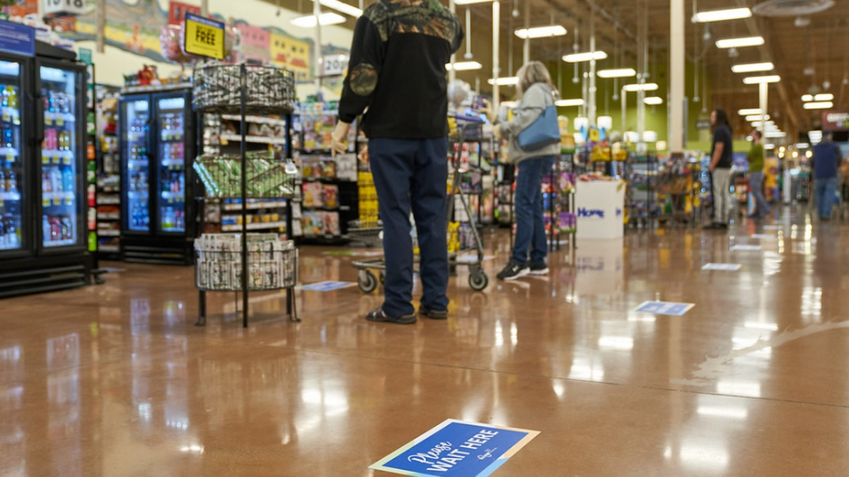 Credit: Kroger grocery store. Signs laid out to display where customers can stand for social...