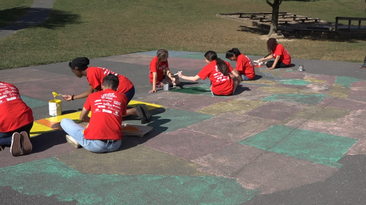 Seniors of Harrisonburg High School painting a map of the USA that needed to be brightened up at John Wayland Elementary School. | Credit: WHSV