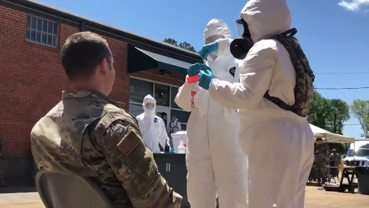 MSgt. Stephen Legge, with the Virginia National Guard, gets swabbed for COVID-19 as part of...