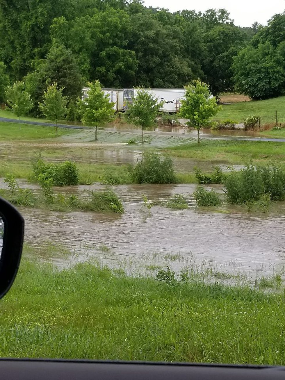 Water pours over a road near Basye, VA