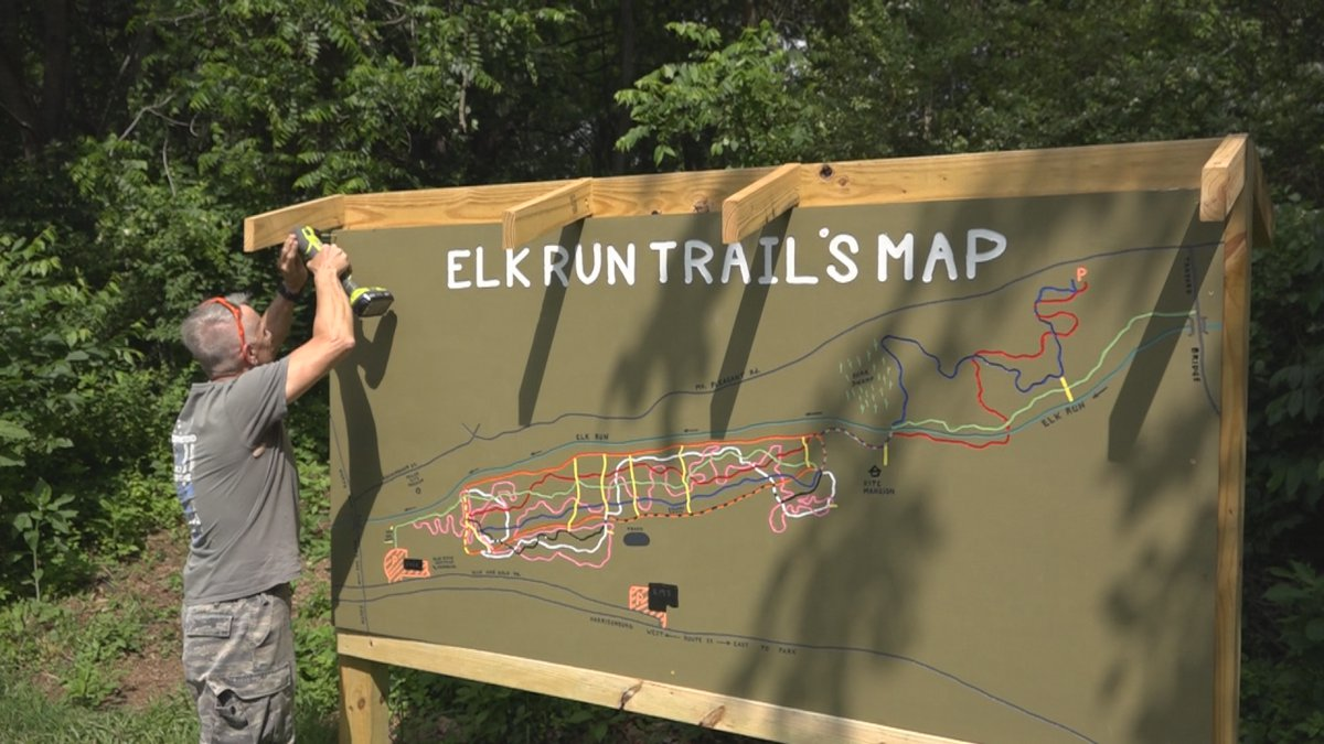 Woody finishes hanging the Elk Run Trail Map Sign.