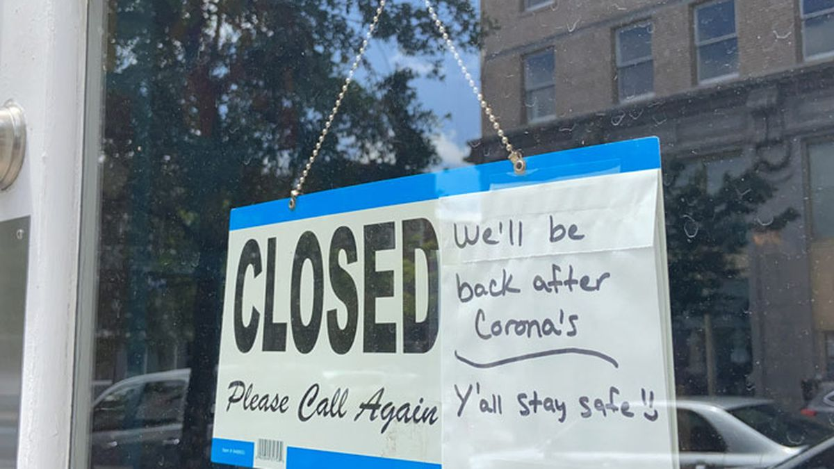 A sign on a building in Wilmington, N.C., shares the news of its temporary closure amid the...