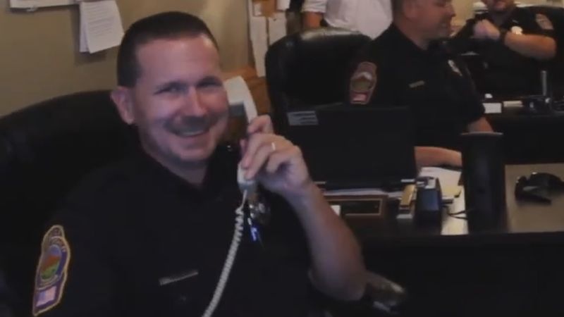 Officer Winum smiling at his desk while answering the phone during the department's 2018 lip...