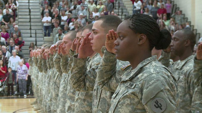 Military members salute.
