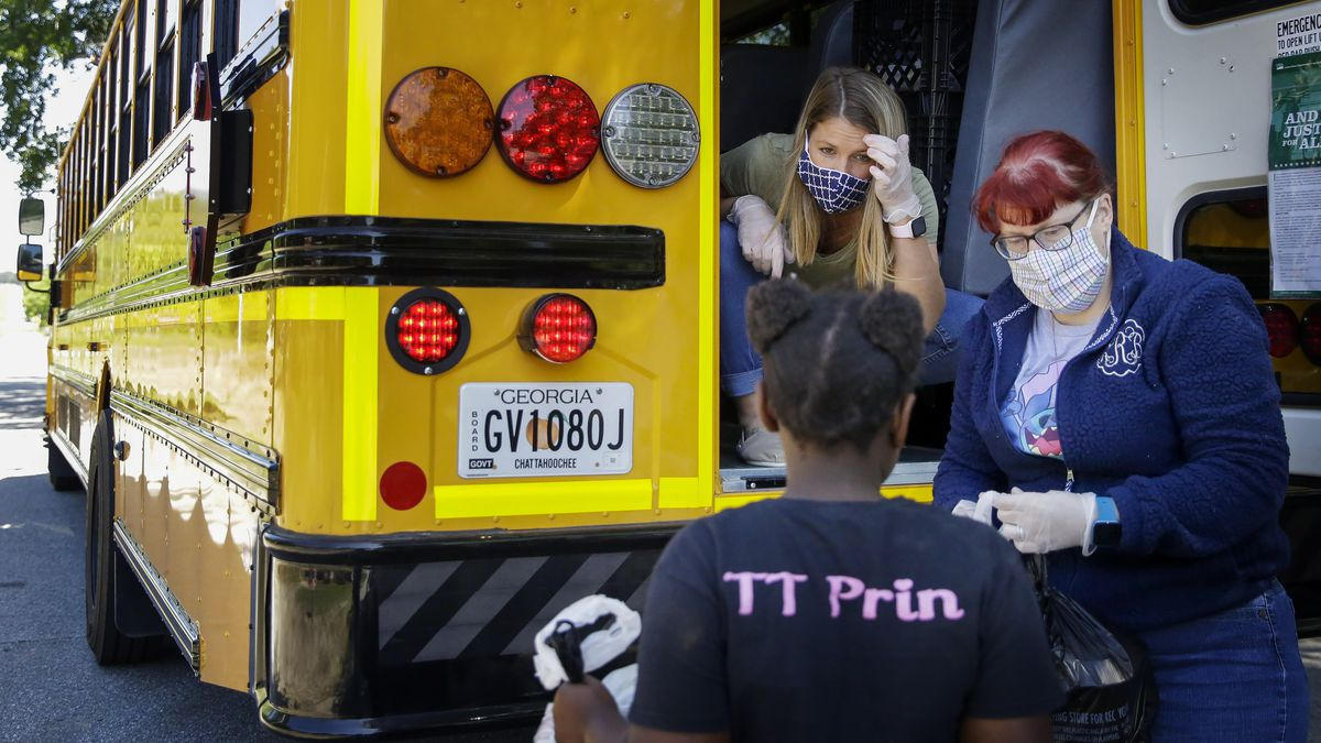 Teachers, Jennifer Scandle, left, and Renee Roberts, right, hand out a lunch to Kelsi Clarke, center, from a school bus as Chattahoochee County schools provide a last meal for their students before summer break on Thursday, May 7, 2020, in Cusseta, Ga.