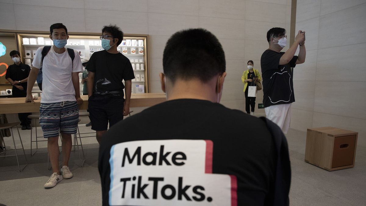 A man wearing a shirt promoting TikTok is seen at an Apple store in Beijing on Friday, July 17, 2020. U. S. President Donald Trump says he wants to take action to ban TikTok, a popular Chinese-owned video app that has been a source of national security and censorship concerns.