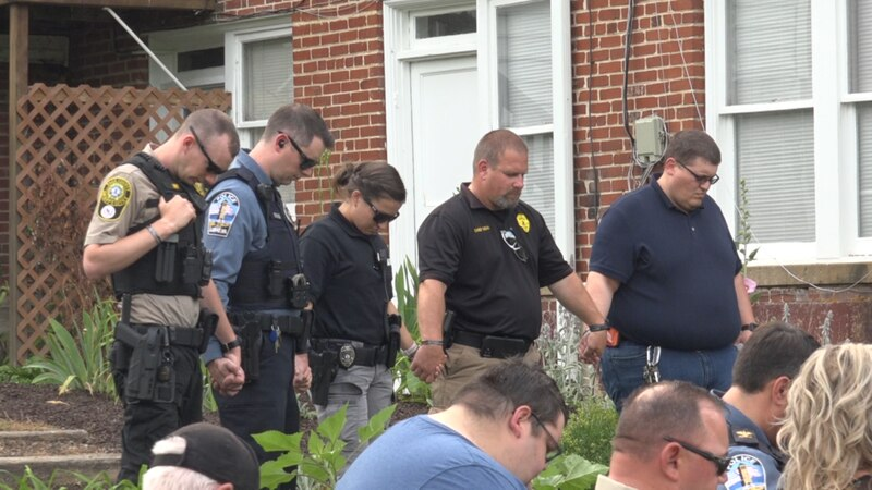 Police officers pray hand in hand for Detective Ronald McClelland.