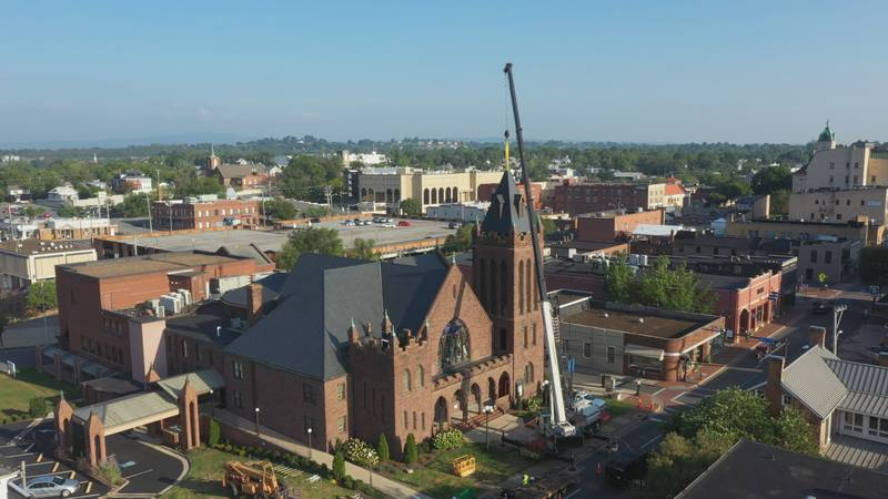 The crane lowering the new bell and steeple on top of the church.