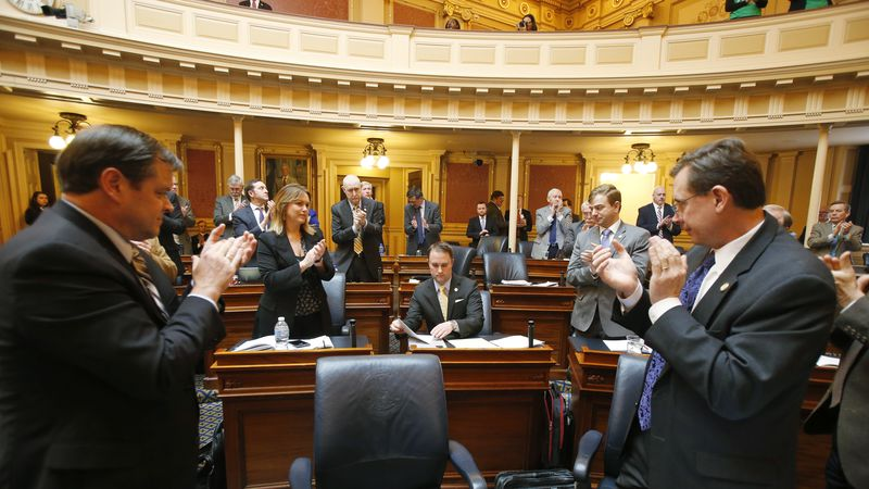 Del. Jason Miyares, R-Virginia Beach, seated center, receives applause from House members...