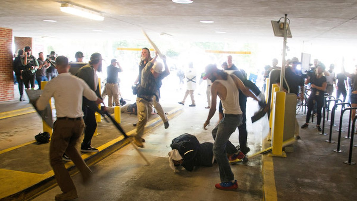 In this Saturday, Aug. 12, 2017 photo, DeAndre Harris, bottom is assaulted in a parking garage...