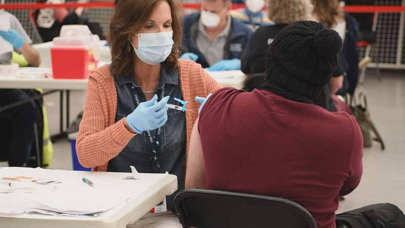 A COVID vaccination is administered at a health department clinic.