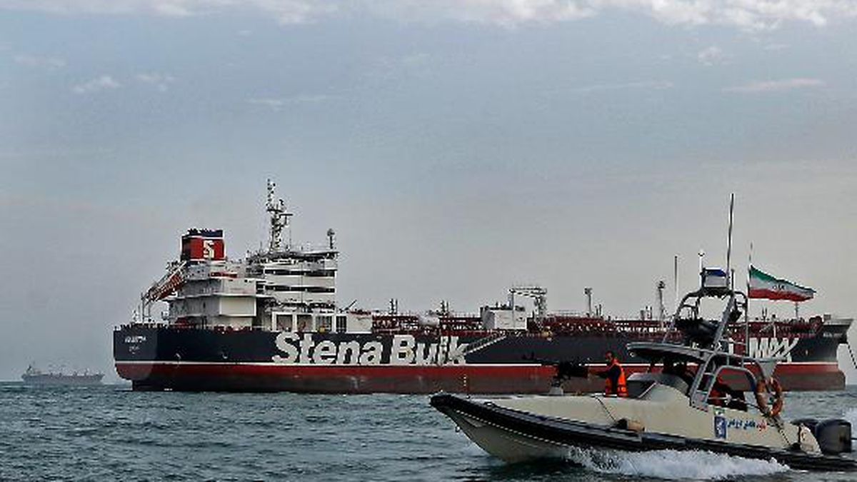 FILE - In this July 21, 2019, file photo, a speedboat of the Iran's Revolutionary Guard moves around a British-flagged oil tanker Stena Impero, which was seized on Friday by the Guard, in the Iranian port of Bandar Abbas. A ship-tracking website shows a British-flagged oil tanker held by Iran since July moving for the first time in weeks. The movement of the Stena Impero on Tuesday, Sept. 24,  comes after a government spokesman in Iran on Monday said legal proceedings against the vessel had concluded.(Hasan Shirvani/Mizan News Agency via AP, File)