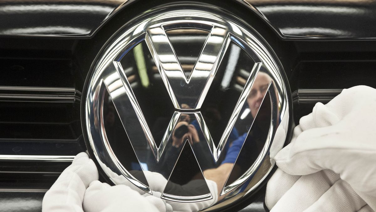 FILE - In this Nov. 9, 2012 file picture a  worker fixes a sign  at a Volkswagen Golf car...