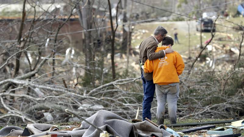 Tennessee Gov. Bill Lee, left, prays with Kayla Cowen, right, as Cowen looks through rubble in...