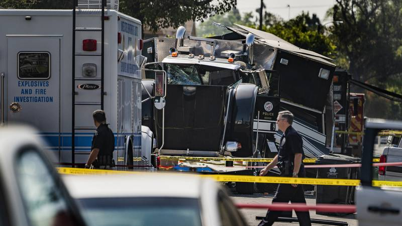 FILE - In this July 1, 2021 file photo, police officers walk past the remains of an armored Los...