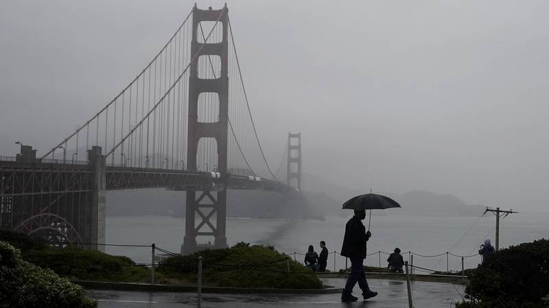 A pedestrian carries an umbrella while walking on a path in front of the Golden Gate Bridge in...