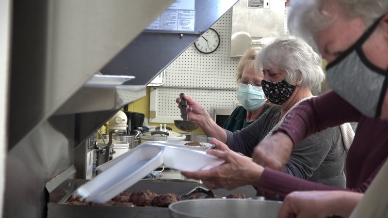 Volunteers stand in line to plate their home cooked meal for members of the Elkton community.