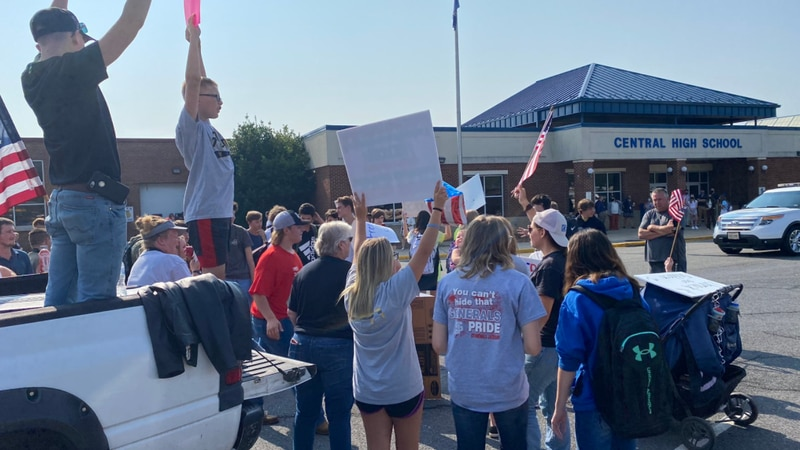 Students and parents standing outside of Central High School with signs in opposition of the...