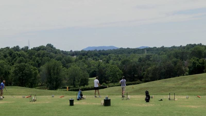 Golfers at Meadowcreek golf course practice before their spread out tee times.