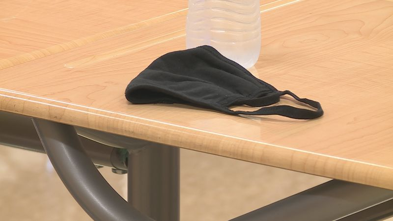 A mask sits on a desk in a classroom
