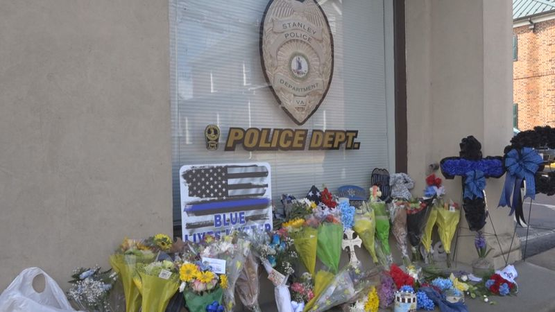 Flowers, signs and mementos laid in front of the Stanley Police Department in honor of Officer...
